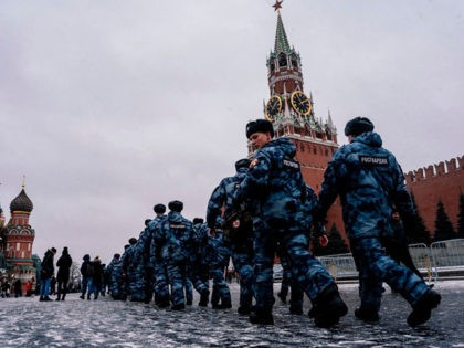 Servicemen of the Russian National Guard patrol along the Red Square in Moscow, on December 30, 2019, as the Kremlin's Spasskaya Tower is seen in the background. - A suspect detained for planning an attack in Saint Petersburg during New Year's festivities had pledged allegiance to the Islamic State group, …