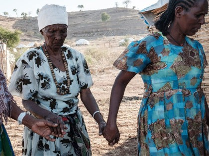 Ethiopian Asafu Alamaya (C), a 80-year-old blind who fled the Tigray conflict, is guided by her daughter at the Um Raquba refugee camp in Sudan's eastern Gedaref state, on December 12, 2020. - The UN says some four percent of over 50,000 people who have fled Tigray for Sudan since …