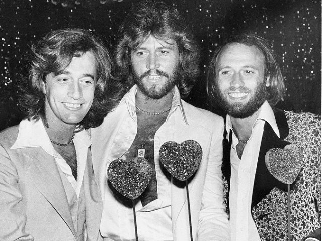 """The Bee Gees, from left, Robin, Barry and Maurice Gibb, attend a party following the Hollywood premiere of """"Sgt. Pepper's Lonely Hearts Club Band"""" on July 31, 1978. The brothers are holding sparkling papier-mache hearts given as party favors. (AP Photo/Lennox McLendon)"""