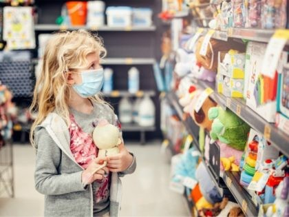 A new normal. Caucasian blonde girl in sanitary face mask shopping at toy store. Child wearing protective mask against coronavirus. Safety, health protection during covid-19 quarantine. - stock photo