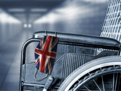 Flag of UK United Kingdom on face mask hanging on empty wheelchair in hallway of British hospital or retirement nursing care home with copy space.
