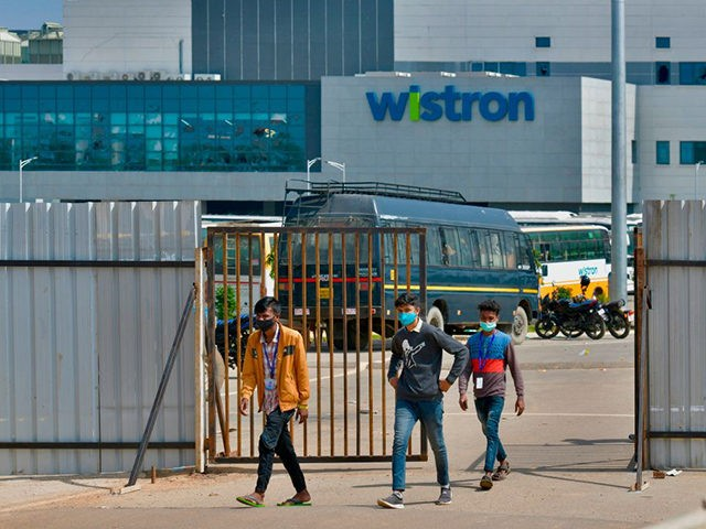 People exit from the gate of Wistron, a Taiwanese-run iPhone factory at Narsapura, about 60 km from Bangalore on December 13, 2020. - Authorities vowed to crack down on workers who went on a violent rampage at a Taiwanese-run iPhone factory in southern India over allegations of unpaid wages and …
