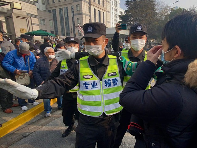 Police attempt to stop journalists from recording footage outside the Shanghai Pudong New District People's Court, where Chinese citizen journalist Zhang Zhan - who reported on Wuhan's Covid-19 outbreak and placed under detention since May - is set for trial in Shanghai on December 28, 2020. (Photo by Leo RAMIREZ …