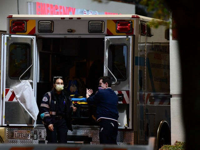 Paramedics wearing facemasks work behind an ambulance at the Garfield Medical Center in Monterey Park, California on March 19, 2020. - All residents of California were ordered to stay at home March 19, 2020, in a bid to battle the coronavirus pandemic in the most populous state in the US. …