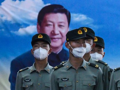EIJING, CHINA - MAY 20: Soldiers of the People's Liberation Army's Honour Guard Battalion wear protective masks as they stand at attention in front of photo of China's president Xi Jinping at their barracks outside the Forbidden City, near Tiananmen Square, on May 20, 2020 in Beijing, China. China's government …