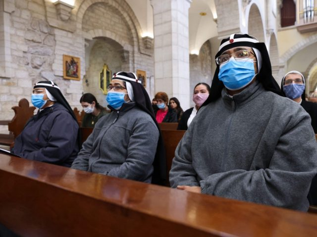 Catholic nuns attend a mass led by the Custos of the Holy Land (unseen) at the Church of the Nativity compound to ceremonially launch the beginning of the Christmas season, in Bethlehem in the Israeli-occupied West Bank,on November 28, 2020. (Photo by Emmanuel DUNAND / AFP) (Photo by EMMANUEL DUNAND/AFP …