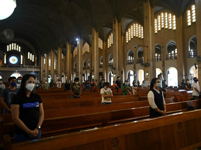Catholic faithful wearing face shields and maintaining physical distancing attend a mass at the usually packed Baclaran church in Paranaque City, suburban Manila on October 9, 2020. - After months of livestreaming mass to millions of faithful from behind closed doors, churches in the Catholic-majority Philippines are beginning to reopen. …