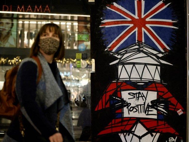 A woman wears a facemask as she walks past graffiti on Victoria Street in central London on December 16, 2020, as new guidance on Christmas during the novel coronavirus COVID-19 pandemic was announced by the government. - Prime Minister Boris Johnson resisted calls to tighten coronavirus restrictions over Christmas, as …