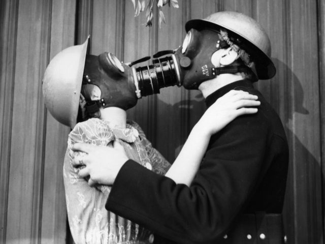 A couple kissing under the mistletoe, wearing gas masks. (Photo by Fox Photos/Getty Images)