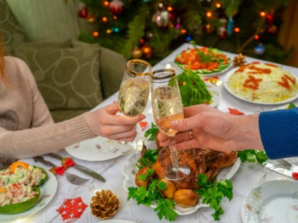 Human hands holding glasses with sparkling wine. Friends or family toasting with champagne against festive Christmas table and decorated new year tree. Winter holidays celebration at cozy home.
