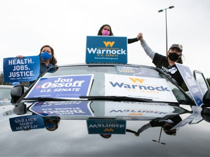 """STONECREST, GA - DECEMBER 28: Supporters wave campaign signs during a """"It's Time to Vote"""" drive-in rally for Georgia Democratic Senate candidates Raphael Warnock and Jon Ossoff on December 28, 2020 in Stonecrest, Georgia. With a week until the January 5th runoff election that will determine control of the Senate, …"""