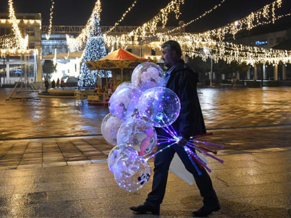 A man walks holding baloons on an almost deserted Podgorica's central square on New Year's Eve on December 31, 2029, as gatherings and celebrations have been restricted amid Covid-19 pandemic. (Photo by Savo PRELEVIC / AFP) (Photo by SAVO PRELEVIC/AFP via Getty Images)