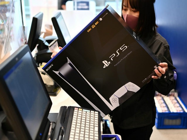 An employee prepares the new Sony PlayStation 5 gaming console for a customer on the first day of its launch, at an electronics shop in Kawasaki, Kanagawa prefecture on November 12, 2020. (Photo by CHARLY TRIBALLEAU / AFP) (Photo by CHARLY TRIBALLEAU/AFP via Getty Images)