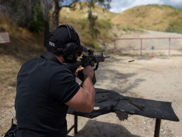 "Rabbi Raziel Cohen, aka ""Tactical Rabbi"", shoots an AR-15 style semi-automatic rifle during a demonstration at the Angeles Shooting Ranges in Pacoima, California on May 20, 2019. - Armed guards, safety assessments and now even a ""Tactical Rabbi"" to train volunteers on the use of weapons -- such is the …"