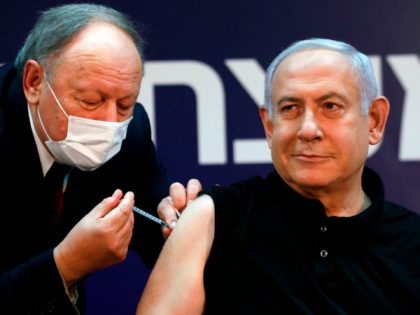 Israeli Prime Minister Benjamin Netanyahu receives a coronavirus vaccine at the Sheba Medical Center, the country's largest hospital, in Ramat Gan near the coastal city of Tel Aviv, on December 19, 2020. - Netanyahu, 71, and Israel's health minister were injected with the Pfizer-BioNTech vaccine live on TV at Sheba …