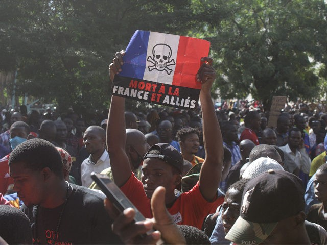 """A man holds up a sign reading in French """"death to France and allies"""" during a gathering outside the Great Mosque of Bamako on October 28, 2020, called to condemn French President Emmanuel Macron remarks after he has strongly defended secular values and the right to mock religion following the …"""