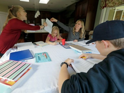In this Oct. 9, 2019 photo, Donya Grant, upper right, works on homeschool lessons with her children, Rowyn, 11, left, Mabry, 8, second from left, and Kemper, 14, right, in their home in Monroe, Wash. The family joined a lawsuit against the Monroe School District and others, alleging that the …