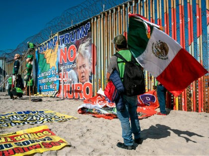 A demonstrator holds a Mexican flag as others hang banners from the border fence during a protest against US President Donald Trump's migration policies, in Playas de Tijuana, Baja California state, on the border with the US, on October 31, 2020 - Trump said in an interview with Mexican newspaper …