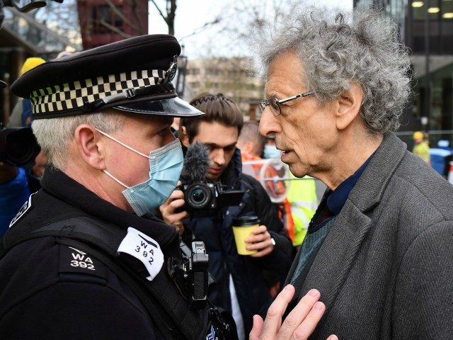 A police officer asks Piers Corbyn (R), brother of former Labour Party leader Jeremy Corbyn, to leave an anti-vaccine demonstration outside the offices of the Bill and Melinda Gates foundation in central London on November 24, 2020. - British Prime Minister Boris Johnson told MPs that thanks to a potential …