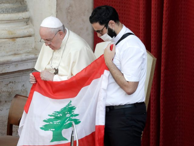 Pope Francis is flanked by Lebanese priest Georges Breidi as they hold a Lebanese flag in remembrance of last month's explosion in Beirut, during the pontiff's general audience, the first with faithful since February when the coronavirus outbreak broke out, at the San Damaso courtyard, at the Vatican, Wednesday, Sept. …