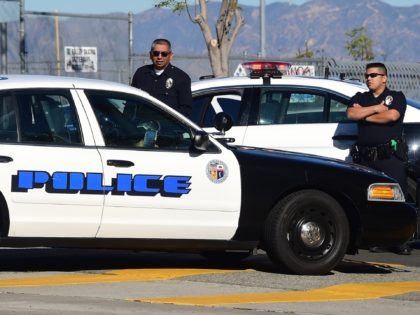 """A police vehicle pulls up next to two officers standing at their vehicle outside a closed school near downtown Los Angeles on December 15, 2015. Los Angeles city officials on Tuesday defended their decision to shut down all public schools following a """"credible"""" emailed threat, as authorities in New York …"""