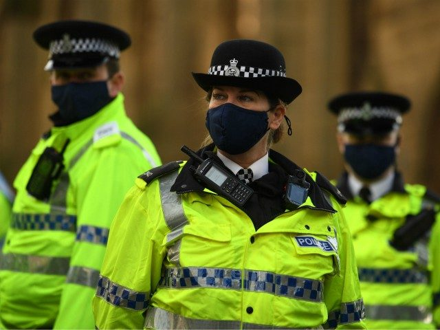 Police officers wearing protective face coverings to combat the spread of the coronavirus covid-19 oversee an anti-vax rally protest against vaccination and government restrictions designed to control or mitigate the spread of the novel coronavirus, including the wearing of masks and lockdowns, in Liverpool on November 14, 2020. (Photo by …