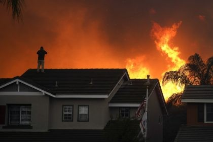 In this Tuesday, Oct. 27, 2020 file photo, Herman Termeer, 54, stands on the roof of his home as the Blue Ridge Fire burns along the hillside in Chino Hills, Calif. An overheating world obliterated weather records in 2020 — an extreme year for hurricanes, wildfires, heat waves, floods, droughts …