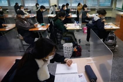 A student checks the time as others wait for the start of the annual college entrance examination amid the coronavirus pandemic at an exam hall in Seoul, South Korea, Thursday, Dec. 3, 2020. South Korean officials are urging people to remain at home if possible and cancel gatherings as about …