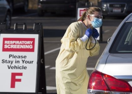 Physician assistant Nicole Thomas conducts a COVID-19 examination in the parking lot at Primary Health Medical Group's clinic in Boise, Idaho, Tuesday, Nov. 24, 2020. The urgent-care clinic revamped into a facility for coronavirus patients as infections and deaths surge in Idaho and nationwide. Some 1,000 people have died due …