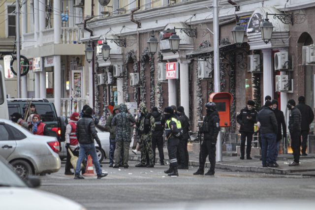 Police and investigators work at the scene after two men attacked road police in the center of the provincial capital, Grozny, Russia, Monday, Dec. 28, 2020. Two brothers attacked police with knives Monday in Chechnya, killing an officer and injuring another before being shot dead, the Russian republic's leader said. …