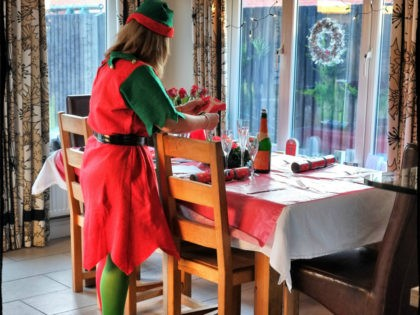 (EDITORS NOTE: This images was created using digital filter) A woman wears an elf suit as she sets the Christmas table on December 25, 2014 in Glasgow, Scotland. Millions of people across the UK spend time with family and loved ones on Christmas day, traditionally exchanging gifts and eating and …