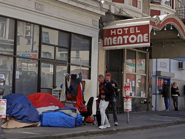 Pedestrians walk to the edge of the sidewalk to avoid stepping on people in tents and sleeping bags on Monday, April 13, 2020, in the tenderloin area of San Francisco. Local governments have begun moving large numbers of homeless into hotels as part of Operation Roomkey. Among the requirements are …