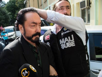 Turkish police officers escort televangelist and leader of a sect, Adnan Oktar (C) on July 11, 2018, in Istanbul, as he is arrested on fraud charges. - Turkish police detained the televangelist on fraud charges on July 11, 2018, notorious for propagating conservative views while surrounded by scantily-clad women he …