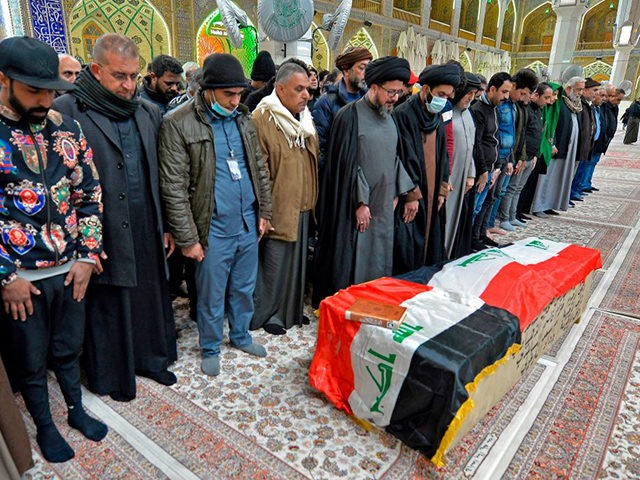 Iraqi mourners pray over the coffin of a victim who was killed in a twin suicide bombing in central Baghdad, during a funeral in the holy city of Najaf on January 21, 2021. - A rare twin suicide bombing killed 32 people and wounded 110 at a crowded market in …
