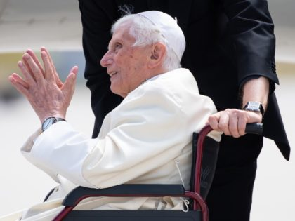 Former pope Benedict XVI sitting in a wheelchair smiles at the airport in Munich, southern Germany, before his departure on June 22, 2020. - Former pope Benedict XVI returns to the Vatican from Germany, where he was visiting his sick brother. (Photo by Sven Hoppe / POOL / AFP) (Photo …
