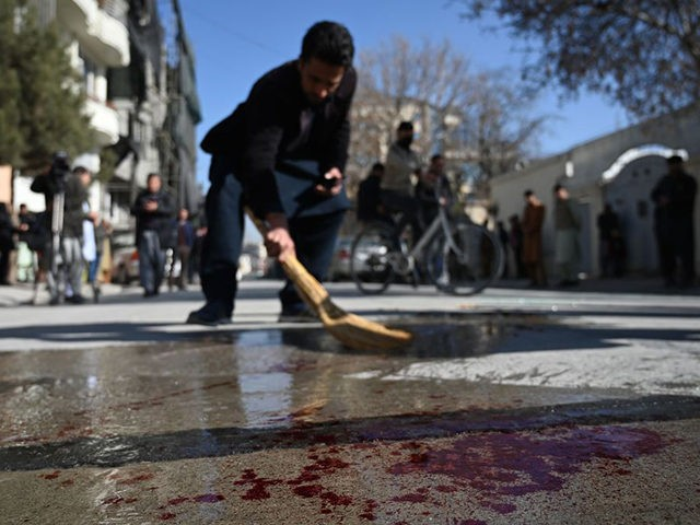 A resident washes a road following gunmen shot dead two Afghan women judges working for the Supreme Court, in Kabul on January 17, 2021. - Gunmen shot dead two Afghan women judges working for the Supreme Court during an early morning ambush in the country's capital on January 17, officials …