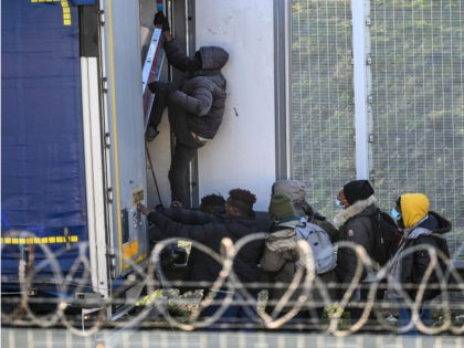 Migrants climb into the back of lorries bound for Britain while traffic is stopped upon waiting to board shuttles at the entrance to the Channel Tunnel site in Calais, northern France, on December 10, 2020. - The French port of Calais continues to attract migrants from the Middle East and …