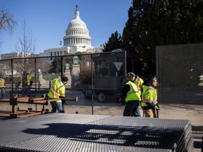 WASHINGTON, DC - JANUARY 07: Workers build a fence around the U.S. Capitol on January 07, 2021 in Washington, DC. Supporters of President Trump had stormed and ransacked the building the day before as Congress debated the a 2020 presidential election Electoral Vote Certification. (Photo by John Moore/Getty Images)