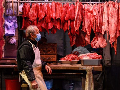 A butcher sits next to fresh meat hanging on display as he waits for customers at his street side shop in Hong Kong on January 18, 2021. (Photo by Anthony WALLACE / AFP) (Photo by ANTHONY WALLACE/AFP via Getty Images)