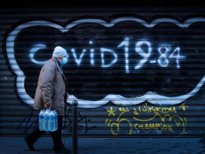 """A man wearing a protective mask walks past a boarded restaurant with the writing """"Covid 19-84"""" referring to George Orwell's book 1984, as France is on a second lockdown aimed at containing the spread of Covid-19 pandemic caused by the novel coronavirus on December 10, 2020. (Photo by JOEL SAGET …"""