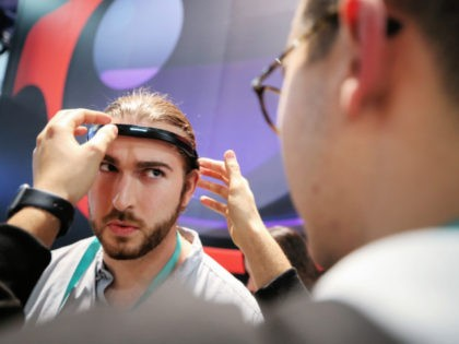 LAS VEGAS, NEVADA - JANUARY 07: A man is fitted with a headband that detects brain activity by a BrainCo employee as he prepares to play their mind control toy car racing game at CES 2020 at the Las Vegas Convention Center on January 7, 2020 in Las Vegas, Nevada. …