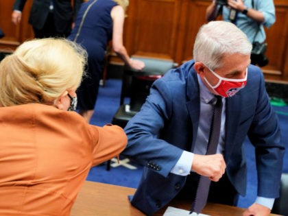WASHINGTON, DC - JULY 31: Anthony Fauci, director of the National Institute of Allergy and Infectious Diseases, and Rep. Carolyn Maloney (D-NY) wear protective masks while greeting each other with an elbow bump after a House Select Subcommittee on the Coronavirus Crisis hearing on July 31, 2020 in Washington, DC. …