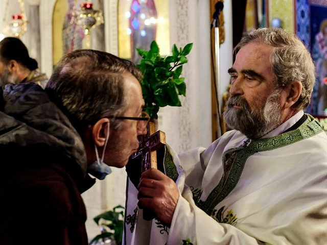 A faithfull kisses a cross during a service at a church in the Greek town of Corinth on January 6, 2021 as Greek bishops' determination to keep churches open for Epiphany holiday in the face of a coronavirus lockdown have stepped up a confrontation with the government over health restrictions. …