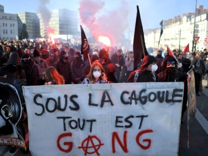 "Protesters known as ""black bloc"" hold a banner reading 'under the hood everything is gang' during a one-day nationwide strike over President Emmanuel Macron's policies on October 9, 2018 in Nantes, western France. (Photo by LOIC VENANCE / AFP) (Photo credit should read LOIC VENANCE/AFP via Getty Images)"
