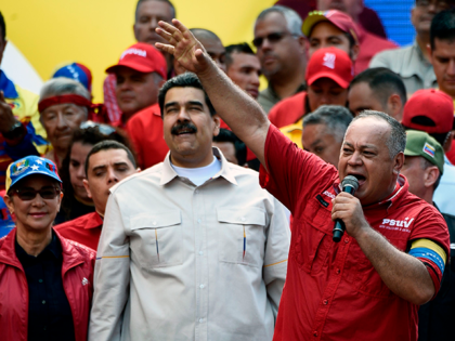 The president of the Venezuelan National Constituent Assembly Diosdado Cabello (R) speaks next to Venezuela's President Nicolas Maduro and First Lady Cilia Flores (L) during a rally at the Miraflores Palace in Caracas, Venezuela on April 6, 2019. - Venezuela's opposition leader Juan Guaido urged his supporters to demonstrate to …
