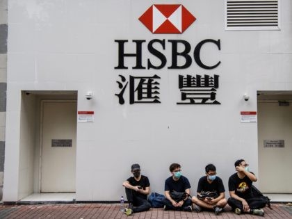 Protesters sit outside a HSBC in the Kowloon district of Hong Kong on August 11, 2019, in the latest opposition to a planned extradition law that was quickly evolved into a wider movement for democratic reforms. - Thousands of pro-democracy protesters hit the streets of Hong Kong for a tenth …