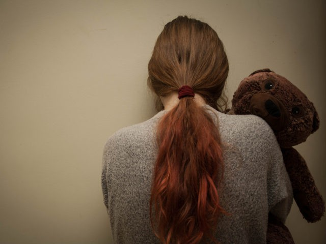 Sad girl with teddy bear standing in the corner.