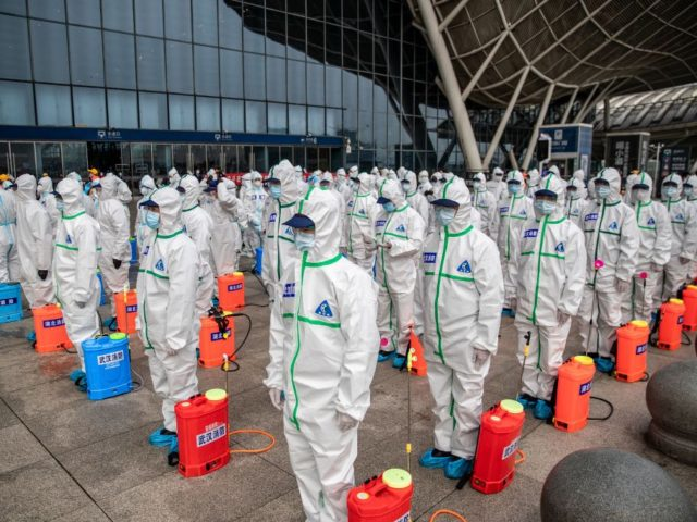 TOPSHOT - Staff members line up at attention as they prepare to spray disinfectant at Wuhan Railway Station in Wuhan in China's central Hubei province on March 24, 2020. - China announced on March 24 that a lockdown would be lifted on more than 50 million people in central Hubei …