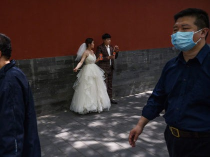BEIJING, CHINA - APRIL 30: A Chinese woman and man wear protective masks as they take a break to have a drink while taking pictures in advance of their wedding near the Forbidden City, on April 30, 2020 in Beijing, China. Beijing lowered its risk level after more than three …