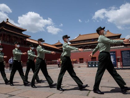 TOPSHOT - People's Liberation Army (PLA) soldiers wearing face masks walk past the entrance to the Forbidden City in Beijing on May 18, 2020. - The annual meeting of the National Peoples Congress, Chinas rubber stamp legislature, opens on May 22, after a two month delay due to the outbreak …